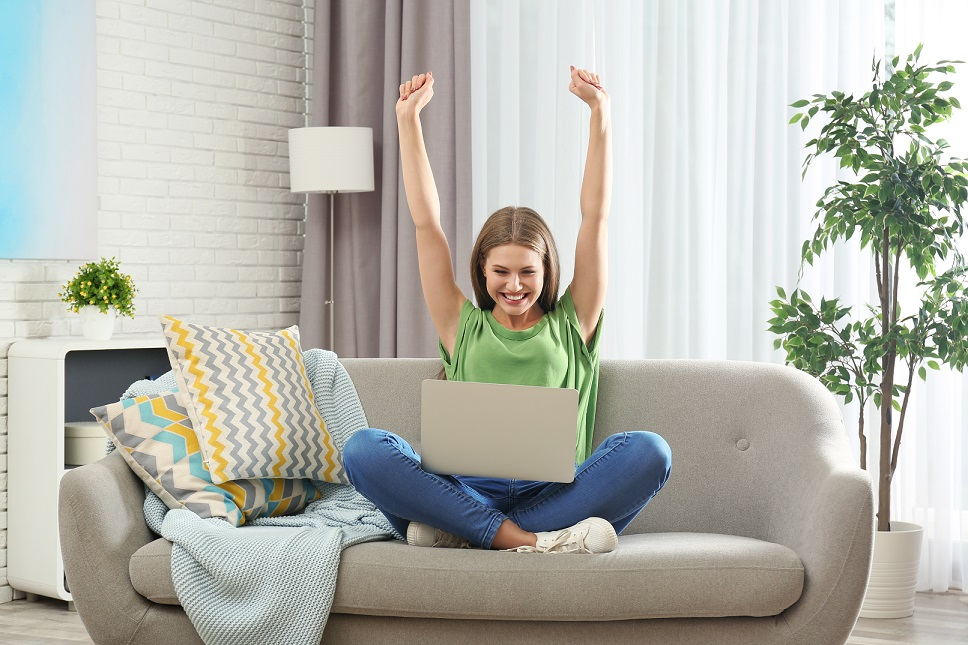 Emotional young woman with laptop celebrating victory on sofa at home